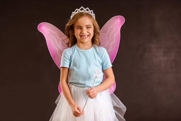 Młoda królowa wróżka z różowymi skrzydłami trzyma magiczną różdżkę.