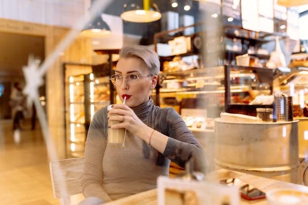 Młoda krótka blond kobieta pije latte przy stole w kawiarni