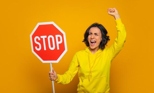 """Młoda krzycząca dziewczyna ubrana w żółtą bluzę, nachalna protestująca z napisem """"stop"""" w dłoniach."""