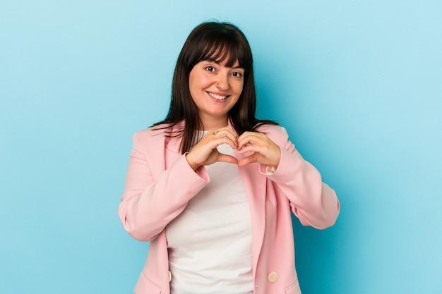 Młoda krzywego kaukaski kobieta na białym tle na niebieskim tle, uśmiechając się i pokazując kształt serca rękami.