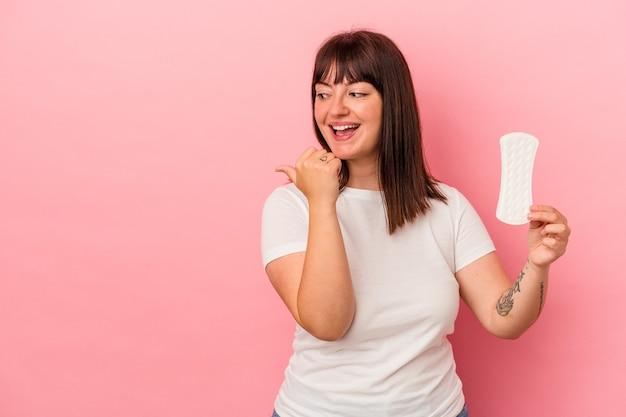 Młoda krzywego kaukaski kobieta trzyma kompres na białym tle na różowym tle wskazuje palcem kciuka, śmiejąc się i beztrosko.