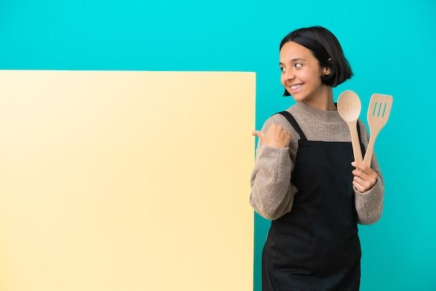 Młoda kucharka rasy mieszanej z dużą tabliczką odizolowaną na niebieskim tle skierowaną w bok, aby zaprezentować produkt
