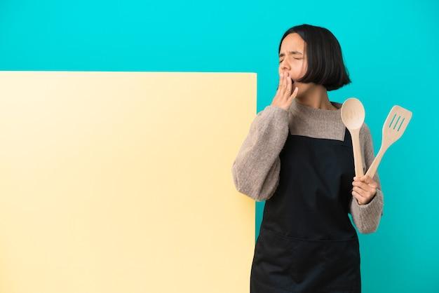 Młoda kucharka rasy mieszanej z dużym plakatem na białym tle ziewa i zakrywa szeroko otwarte usta dłonią