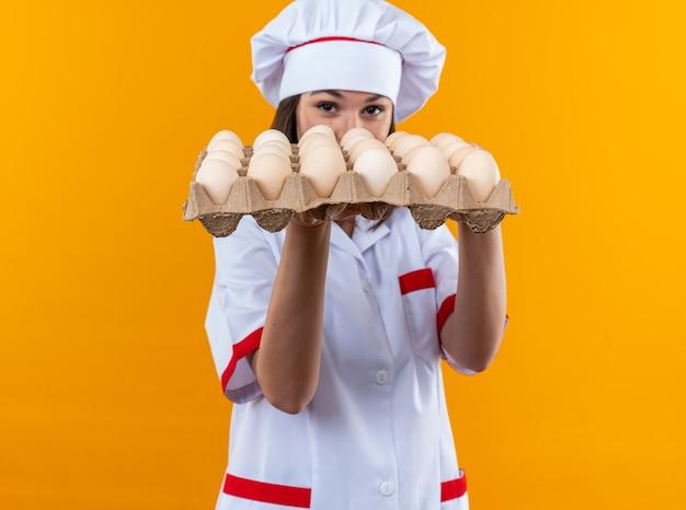 Młoda kucharka ubrana w mundur szefa kuchni trzymająca i zakrytą twarz z partią jajek odizolowaną na pomarańczowej ścianie
