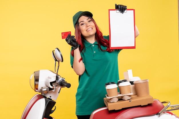 Młoda kurierka z dostawą kawy i jedzenia na żółto