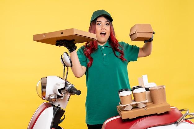 Młoda kurierka z dostawą kawy i paczki z jedzeniem na żółto