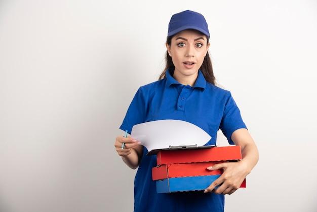 Młoda kurierka z kartonem pizzy i schowkiem