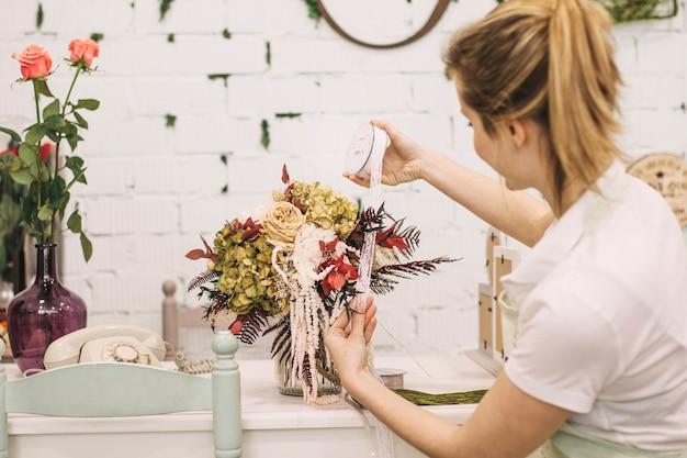 Młoda kwiaciarnia dekoruje bukiet