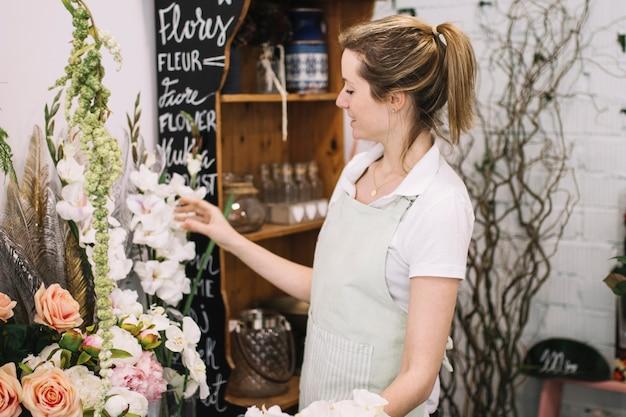 Młoda kwiaciarnia pracuje w kwiatu sklepie