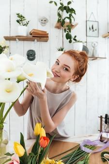 Młoda kwiaciarnia wącha białe kwiaty podczas pracy