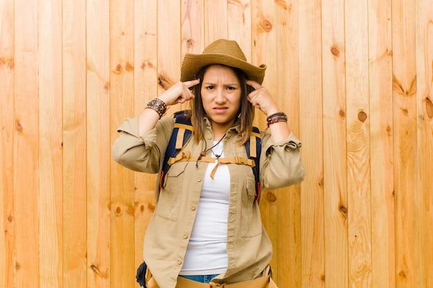Młoda łacińska badacz kobieta przeciw drewnianej ścianie