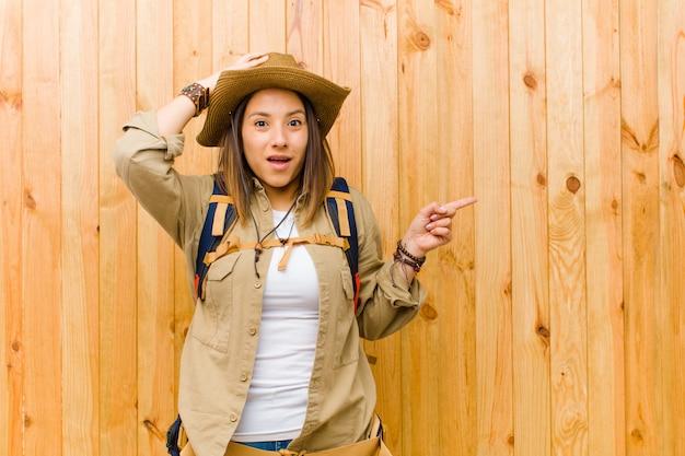Młoda łacińska badacz kobieta przeciw drewnianemu ściennemu tłu