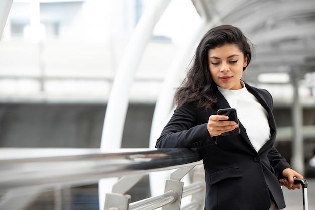 Młoda łacińska bizneswoman używa telefon komórkowego i trzyma rękojeść tramwaj torba