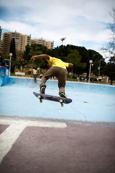 Młoda łacińska chłopiec robi akrobacje z jego łyżwą w skate parku.