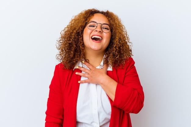 Młoda łacińska kobieta krzywego na białym tle śmieje się głośno trzymając rękę na klatce piersiowej.