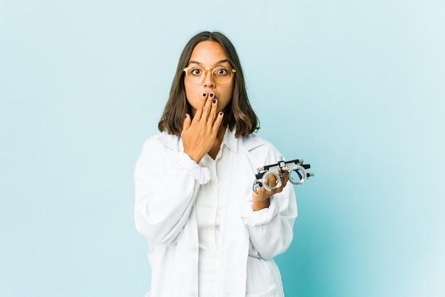 Młoda łacińska kobieta okulistka na odizolowanej ścianie wstrząśnięty obejmując usta rękami.
