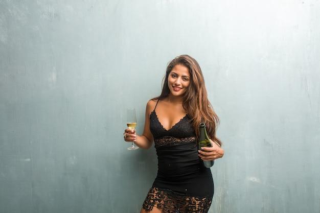 Młoda łacińska kobieta świętuje nowego roku lub wydarzenie. podekscytowany i szczęśliwy, trzymając butelkę szampana i kubek.