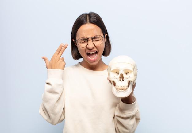 Młoda łacińska kobieta szuka nieszczęśliwego i zestresowanego, samobójczy gest czyniąc pistolet znak ręką
