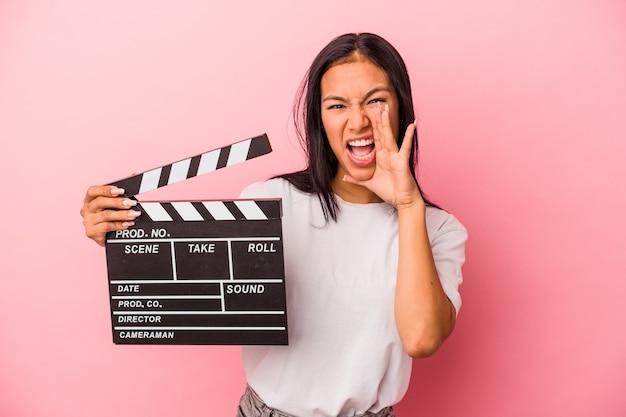 Młoda łacińska kobieta trzyma klaps na białym tle na różowym tle krzycząc i trzymając dłoń w pobliżu otwartych ust.