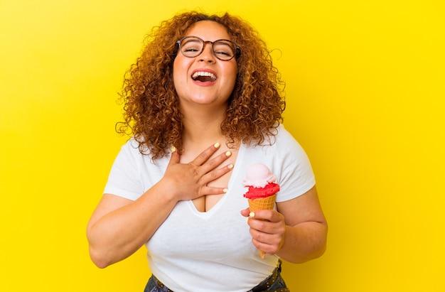 Młoda łacińska kobieta trzyma lody na białym tle na żółtym tle śmieje się głośno trzymając rękę na piersi.