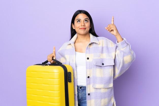 Młoda łacińska kobiety kobieta odizolowywająca na purpurach w wakacje z podróży walizką i wskazuje up