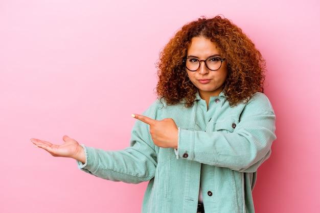 Młoda łacińska krzywego kobieta na białym tle na różowej ścianie podekscytowany trzyma miejsce na kopię na dłoni.