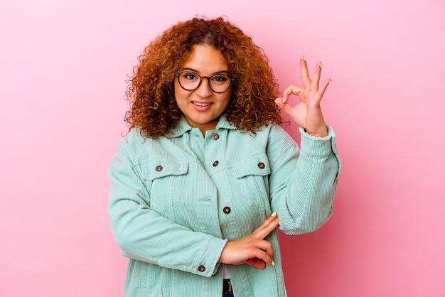 Młoda łacińska krzywego kobieta na białym tle na różowym tle mruga okiem i trzyma w porządku gest ręką.