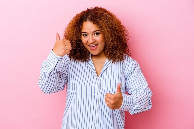 Młoda łacińska krzywego kobieta na białym tle na różowym tle, podnosząc kciuki do góry, uśmiechnięta i pewna siebie.