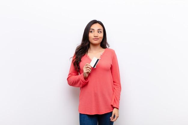 Młoda łacińska ładna kobieta przeciw płaskiej ścianie z kartą kredytową