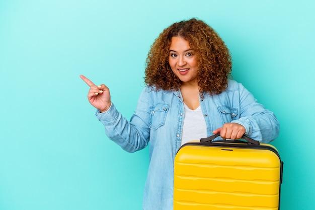 Młoda łacińska podróżnik kręty kobieta trzyma walizkę na białym tle na niebieskiej ścianie, uśmiechając się i wskazując na bok, pokazując coś w pustej przestrzeni