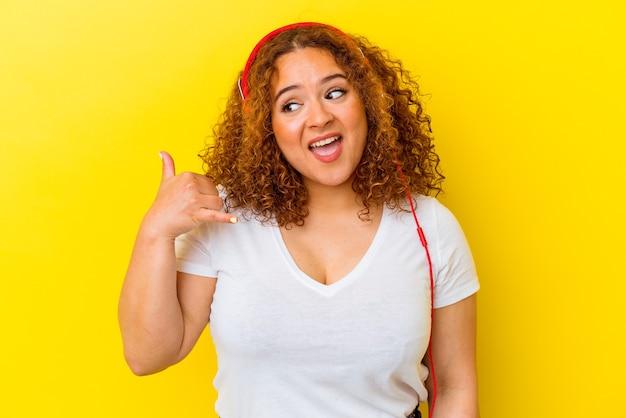 Młoda łacińskiej krzywego kobieta słuchania muzyki na białym tle na żółtym tle pokazując gest połączenia z telefonu komórkowego palcami.