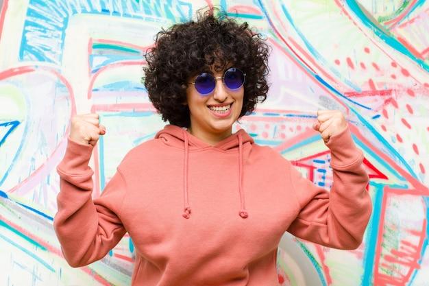 Młoda ładna afro kobieta czująca się szczęśliwa, pozytywna i odnosząca sukcesy, świętująca zwycięstwo, osiągnięcia lub powodzenia w walce z graffiti