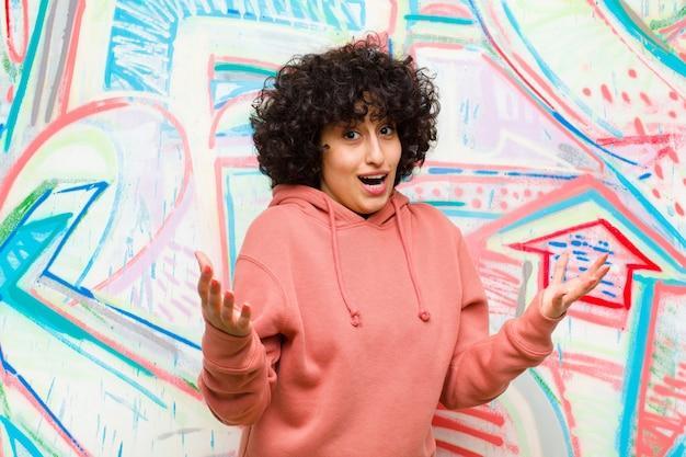 Młoda ładna afro kobieta czująca się szczęśliwa, zdziwiona, szczęśliwa i zaskoczona, lubiąca mówić poważnie? niewiarygodne na tle graffiti