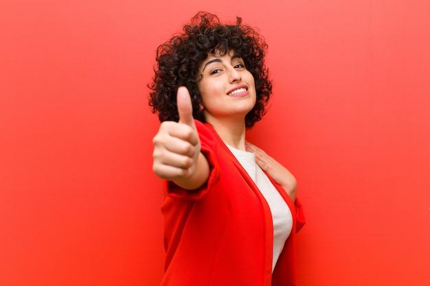 Młoda ładna afro kobieta czuje się dumna, beztroska, pewna siebie i szczęśliwa, uśmiechając się pozytywnie z kciukami do góry