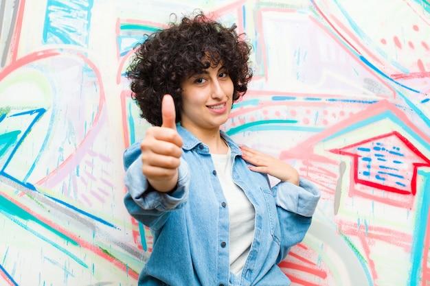 Młoda ładna afro kobieta czuje się dumna, beztroska, pewna siebie i szczęśliwa, uśmiechając się pozytywnie z kciukami do graffiti