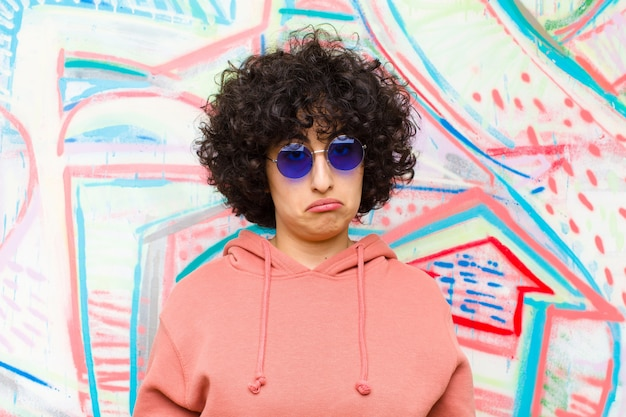 Młoda ładna afro kobieta czuje się smutna i zestresowana, zdenerwowana z powodu złej niespodzianki, z negatywnym, niespokojnym wyglądem ściany graffiti