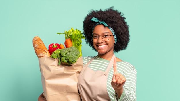 Młoda ładna Afro Kobieta Czuje Się Szczęśliwa, Podekscytowana I Pozytywna, Wydając Wielki Okrzyk Z Rękami Przy Ustach, Wołając I Trzymając Torbę Warzyw Premium Zdjęcia