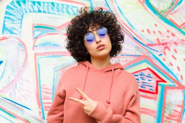 Młoda ładna afro kobieta czuje się szczęśliwa, pozytywna i udana, z ręką wykonującą kształt v nad klatką piersiową, pokazując zwycięstwo lub pokój przeciwko ścianie graffiti