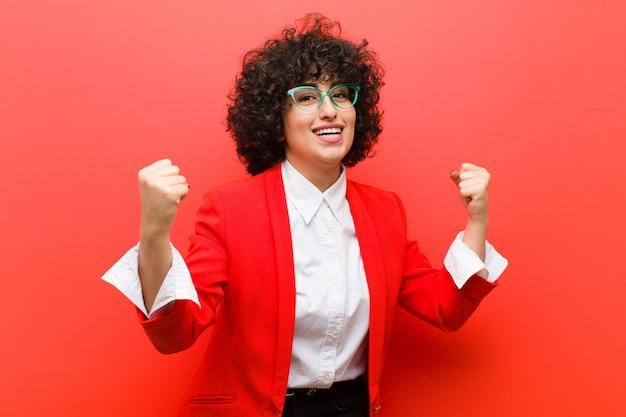 Młoda ładna afro kobieta czuje się szczęśliwa, zaskoczona i dumna, krzyczy i świętuje sukces z wielkim uśmiechem