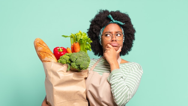 Młoda ładna afro kobieta myśli, czuje się zwątpienie i zdezorientowana, z różnymi opcjami, zastanawiając się, którą decyzję podjąć i trzymając torbę z warzywami
