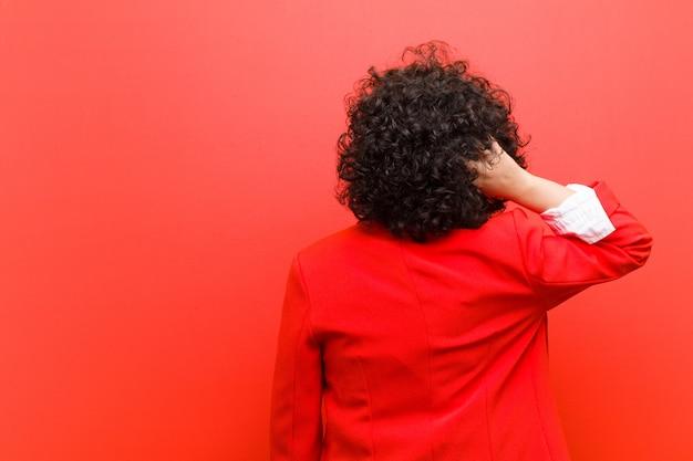 Młoda ładna afro kobieta myśli lub wątpi, drapiąc się po głowie, czując się zdziwiona i zdezorientowana, widok z tyłu lub z tyłu