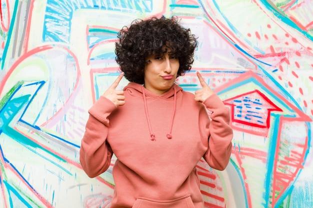 Młoda ładna afro kobieta o złym nastawieniu, wyglądająca dumnie i agresywnie, skierowana w górę lub szykująca się do zabawy z rękami na ścianie graffiti