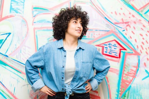 Młoda ładna afro kobieta patrzeje szczęśliwy rozochocony i ufny ono uśmiecha się dumnie i patrzeje popierać obiema rękami na biodrach przeciw graffiti ścianie
