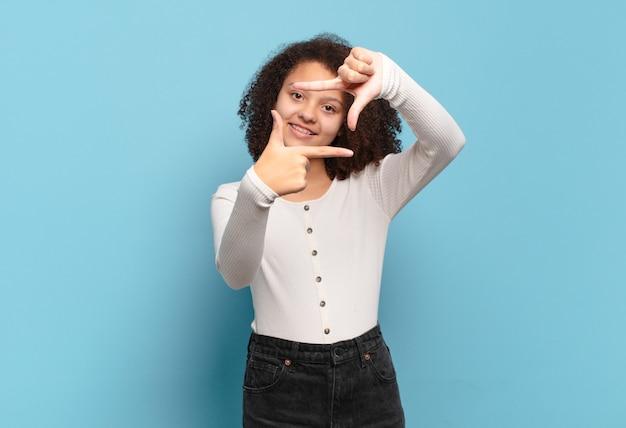 Młoda ładna afro kobieta robi ramki rękami