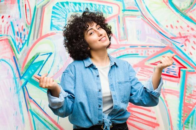 Młoda ładna afro kobieta uśmiecha się, czuje się beztrosko, zrelaksowana i szczęśliwa, tańczy i słucha muzyki, dobrze się bawiąc na imprezie przy ścianie graffiti