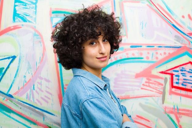 Młoda ładna afro kobieta uśmiecha się do kamery ze skrzyżowanymi rękami i szczęśliwy, pewny siebie, zadowolony wyraz twarzy z boku na ścianie graffiti