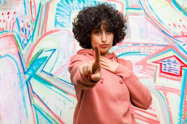 Młoda ładna afro kobieta uśmiecha się dumnie i pewnie, robiąc pozę numer jeden triumfalnie, czując się jak lider na tle graffiti