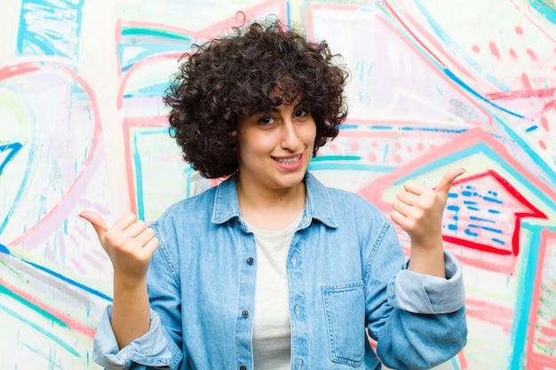 Młoda ładna afro kobieta uśmiecha się radośnie i wygląda na szczęśliwą, czując się beztrosko i pozytywnie, kciukami do graffiti
