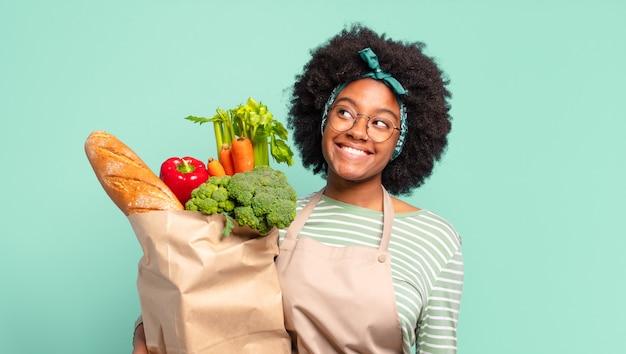 Młoda ładna afro kobieta uśmiecha się radośnie z ręką na biodrze i pewną siebie, pozytywną, dumną i przyjazną postawą oraz trzyma worek z warzywami