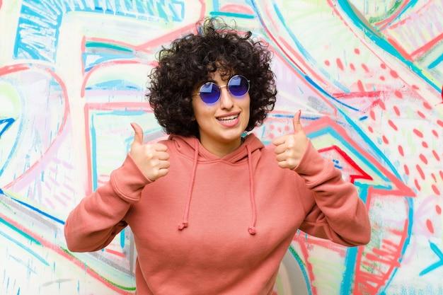 Młoda ładna afro kobieta uśmiecha się szeroko, szczęśliwa, pozytywna, pewna siebie i odnosząca sukcesy, z kciukami skierowanymi przeciwko graffiti
